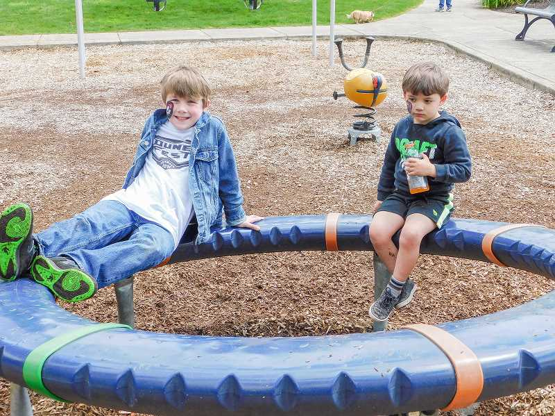 ESTACADA NEWS PHOTO: EMILY LINDSTRAND - Ethan and Collin Deshirlia spend time on the playground at the anniversary celebration for Wade Creek Park on Saturday, May 6.