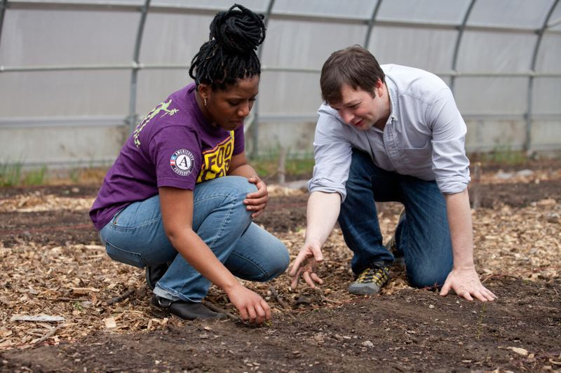 COURTESY OF FOODCORPS - FoodCorps co-founder Curt Ellis works with  staffer Kala Cuerington to plant seeds inside a large hoophouse.