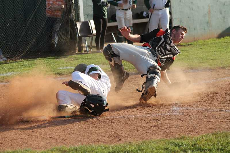 PIONEER PHOTO: CONNER WILLIAMS  - Estacada sophomore Nick Keller slides into home after Levi Albrecht's walk-off single to win the Tri-Valley title Tuesday.