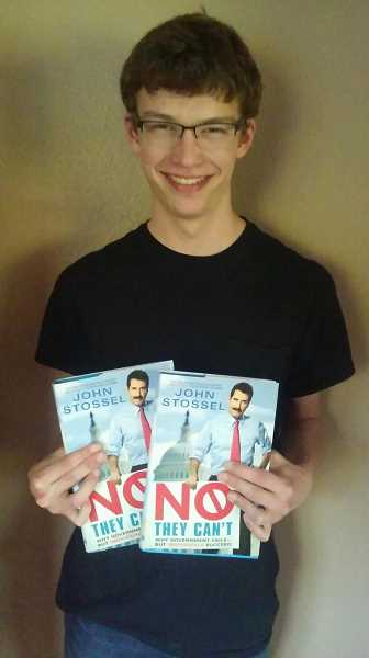 COURTESY PHOTO - Gaston resident Jacob McDowell, 17, holds two copies of journalist John Stossels book, which hes won in an essay contest two years in a row.