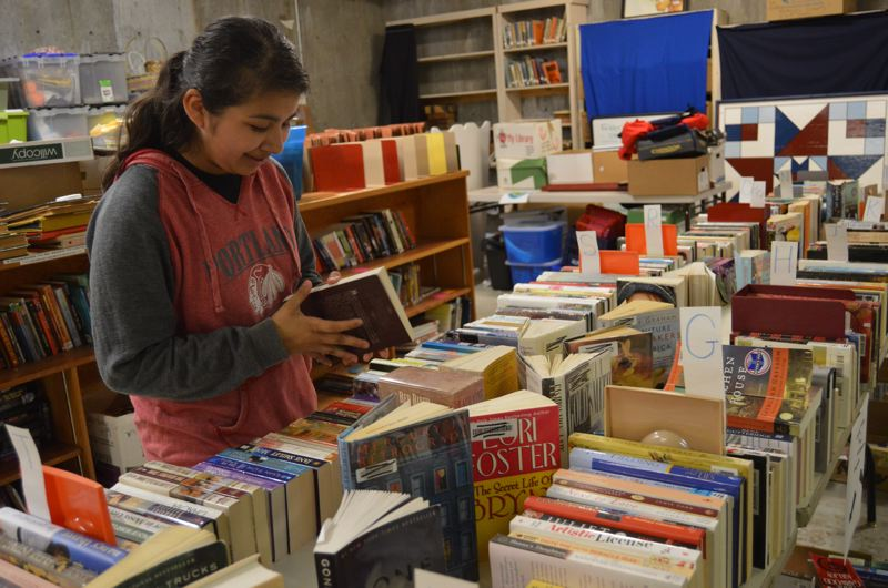 SPOTLIGHT PHOTO: COURTNEY VAUGHN - Kalina Rico, a Scappoose Middle School student, previews books that will be up for sale to the public during the Friends of the Scappoose Public Library's spring book sale next Saturday, May 20. The book sale will offer books of all genres for no more than $2.