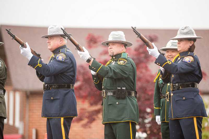 OUTLOOK PHOTO: JOSH KULLA - A ceremonial guard fires a volley of shots from M1 Garand rifles Thursday during a memorial service for fallen law enforcement officers held in Troutdale by the Multnomah County Sheriff's Office.