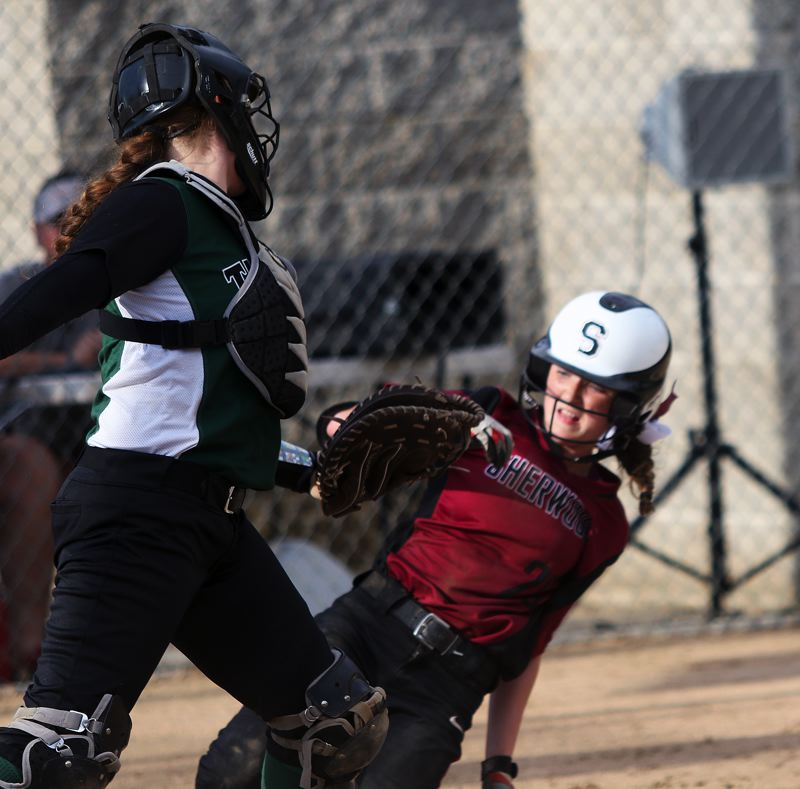 DAN BROOD - Sherwood freshman Jordyn Moullet-Dozier (right) slides home safely during the Lady Bowmen's game with Tigard.