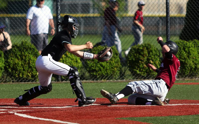 DAN BROOD - Tigard senior catcher Parker Kuntz (left) grabs for the ball as Sherwood junior Jacob Matzat slides to home plate during Tuesday's game. The Tigers won 5-2.