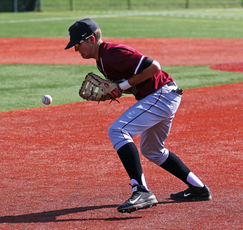 DAN BROOD - Sherwood senior first baseman Kevin Skurdahl knocks the ball down before making a play during the Bowmen's game with Tigard.