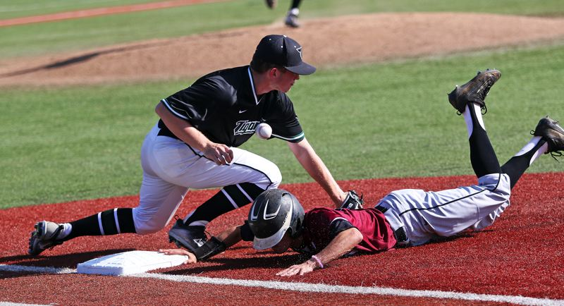 DAN BROOD - Tigard High School senior first baseman Connor Wojahn (left) grabs for the ball as Sherwood sophomore Anthony Garrett dives back to first base on a pickoff play during Tuesday's game.