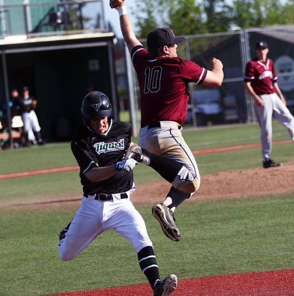 DAN BROOD - Tigard senior Parker Kuntz (left) gets to first base as Sherwood senior Harrison Grow goes up to get the ball during Tuesday's game.