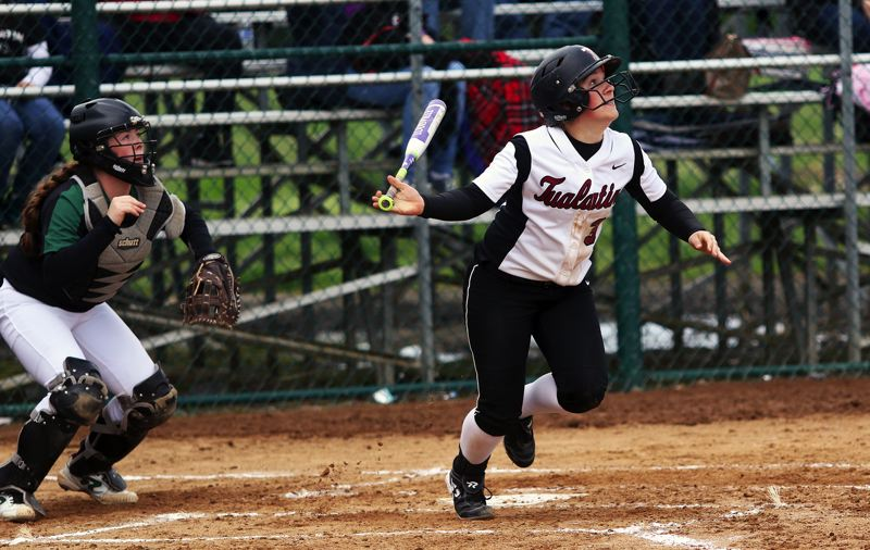 DAN BROOD - Tualatin High School senior Amanda Reser (right), in front of Tigard freshman catcher Emily Paulson, puts the ball in play during the Timberwolves' 4-0 victory.