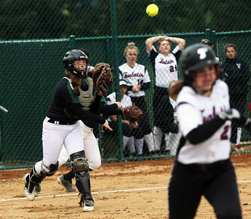 DAN BROOD - Tigard freshman catcher Emily Paulson makes a throw to first during the Tigers' game at Tualatin.