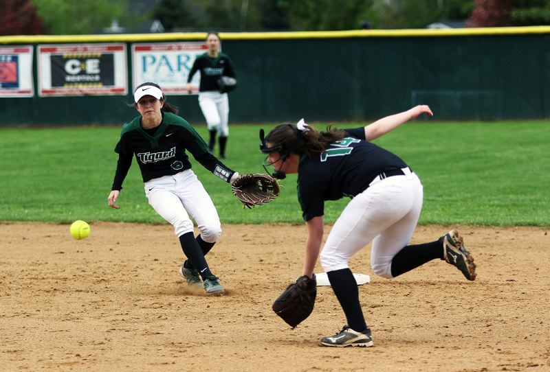 DAN BROOD - Tigard junior second baseman Caroline Riggs (right) runs in on the ball during the Tigers' game at Tualatin.