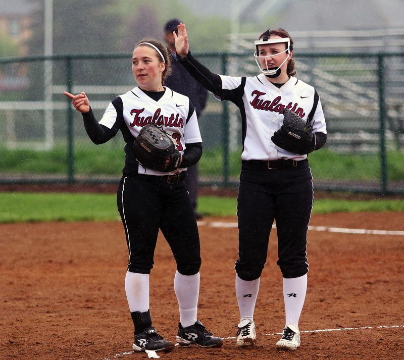 DAN BROOD - Tualatin senior second baseman Amanda Reser (left) and junior pitcher Megan Woodward call for a time out during the Wolves' game with Tigard.