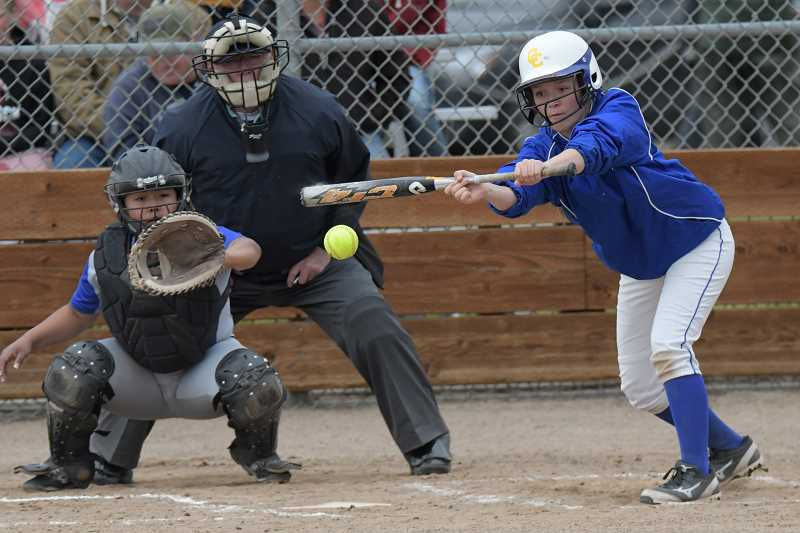 LON AUSTIN/CENTRAL OREGONIAN - Matney Searcy lays down a bunt single during the Cowgirls seven run third inning.