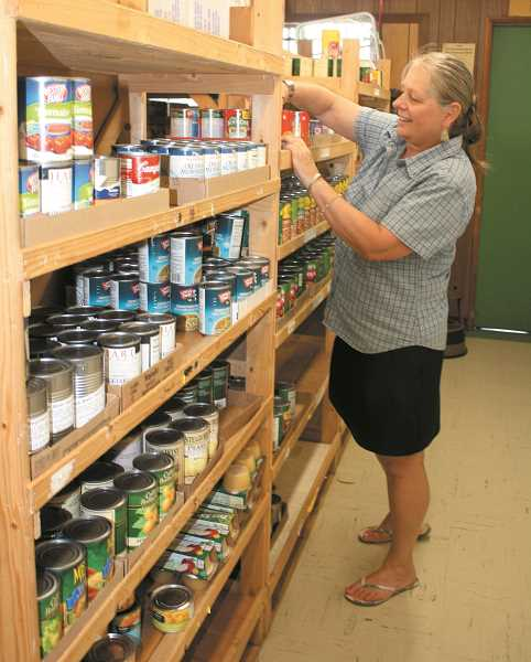 PEGGY SAVAGE - Molalla Service Center Director Rise Estergreen, stocks pantry shelves in the center's food bank.