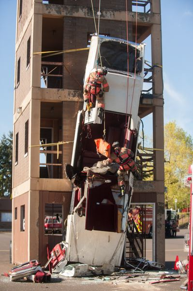 OUTLOOK PHOTO: JOSH KULLA - Firefighters Grant Kimble and Tyson Guillory rappel down the Gresham Fire Department's training tower to get to the simulated occupants of a limousine below. The training exercise took place Friday at the department's training facility on Northeast Halsey Street.