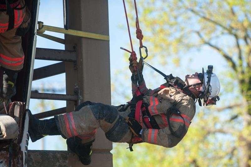 OUTLOOK PHOTO: JOSH KULLA - Firefighter Tyson Guillory rappels down the face of the Gresham Fire Department's training tower Friday during a simulated urban search and rescue exercise.