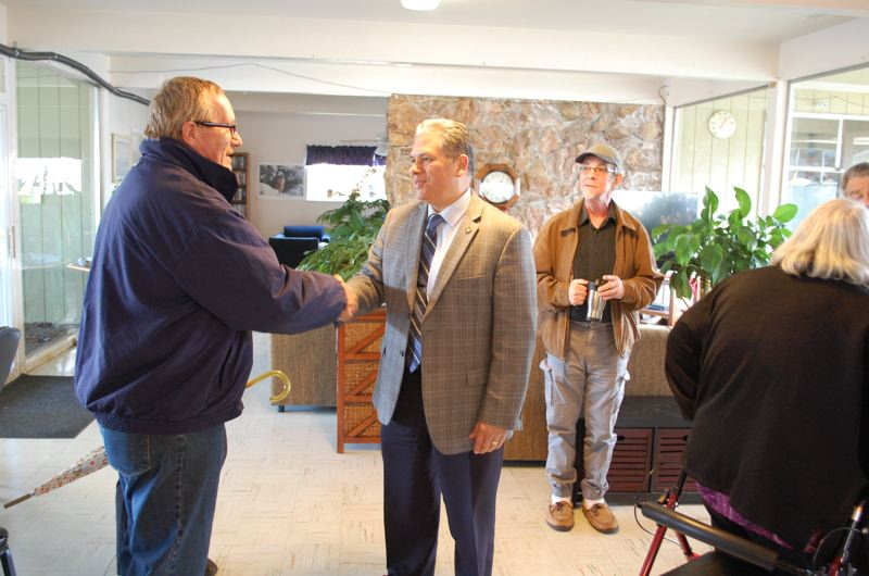 PHOTO BY: RAYMOND RENDLEMAN - Gladstone Mobile Home Park resident Kim Baller shakes Mark Meek's hand as park owner Lowell Read looks on.