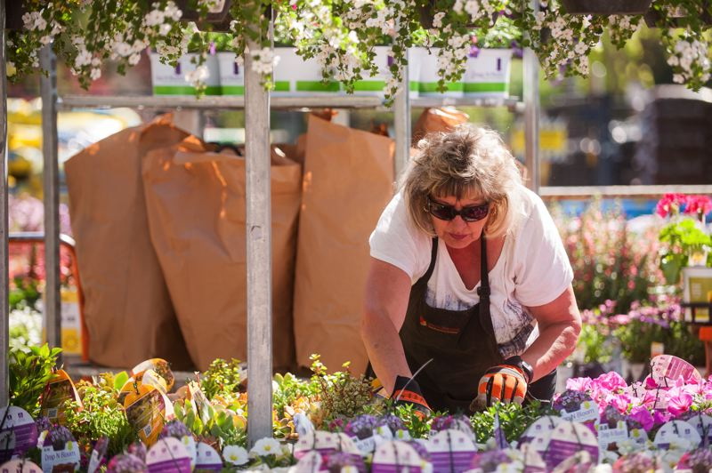 OUTLOOK PHOTO: JOSH KULLA - Home Depot veteran Heidi Petty arranges flowers in the garden section of the national retailer's Troutdale store. The company is gearing up for the busy summer season, where it is expected to hire some 80,000 workers at stores across the country.