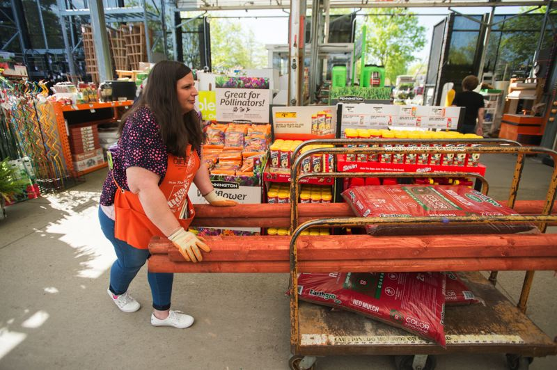 OUTLOOK PHOTO: JOSH KULLA - Garden Superviser Cherie Goodale pushes a cart across the garden center at the Troutdale Home Depot store. The national retailing giant is gearing up to hire more than 80,000 workers nationwide in preparation for the busy summer season.