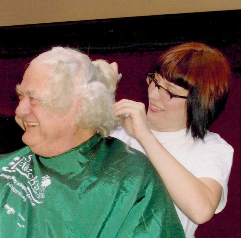 COURTESY OF PAUL HEINMAN - A beautician gets ready to shave Paul Heineman's hair at at St. Baldrick's fundraiser after he grew it out for 18 months.