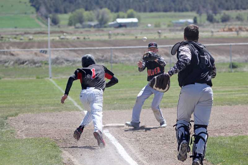 WILL DENNER/MADRAS PIONEER - Culver catcher Mack Little throws to Tadd Anderson at third base in time to tag out Dufur's Bailey Keever, who got caught in between the bases during game one of a doubleheader last Friday.