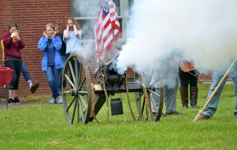 REVIEW PHOTO: VERN UYETAKE - Students plug their ears as the Civil War cannon is set off.