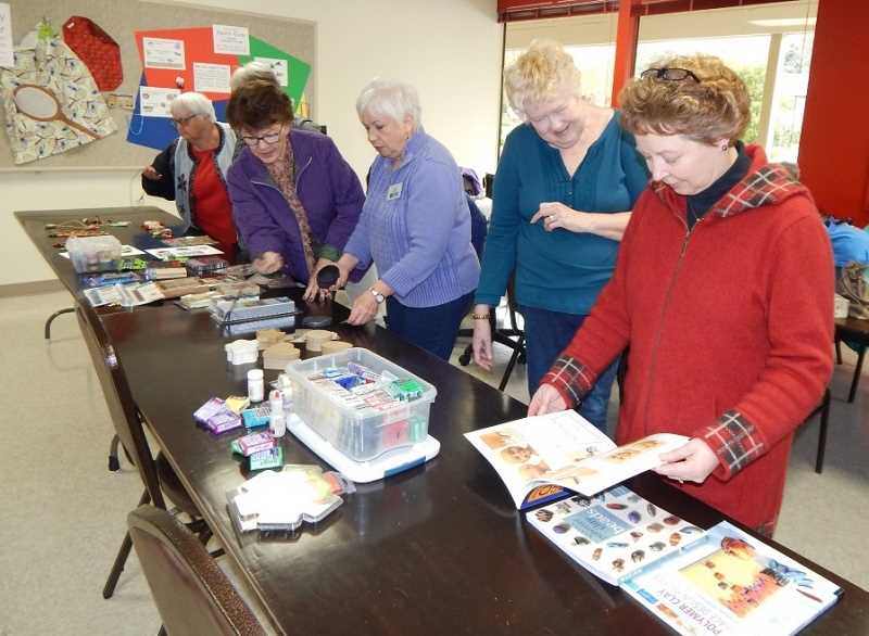BARBARA SHERMAN - At the beginning of the Summerfield Craft Club meeting, those interested in making something out of polymer clay looked through books for ideas, and Susan Burson (far right) eyes some heads on a page, which is exactly what she ended up making.