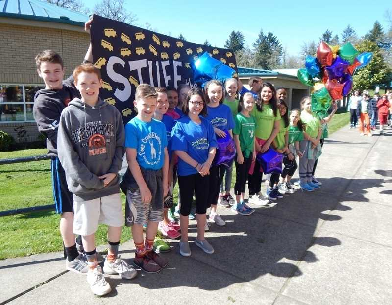 BARBARA SHERMAN - Deer Ceek Elementary student ambassadors, who organized the Stuff the Bus drive at their school, pose with a banner promoting the annual event in front of the school.