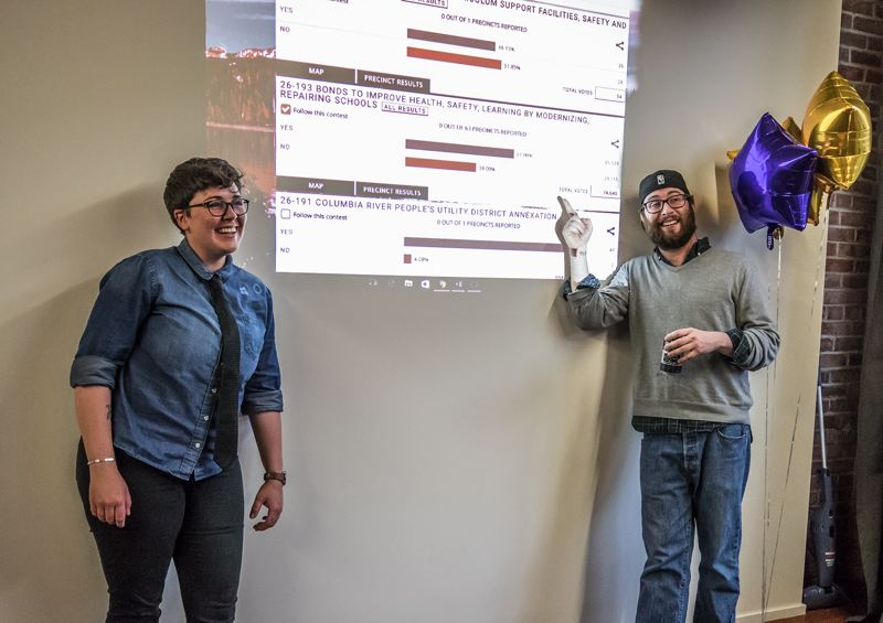 JONATHAN HOUSE - Supporters of the Portland Public Schools' bond, Brandi Jordan, left, and Ben Katz, pose for a picture in front of early results from Multnomah County.