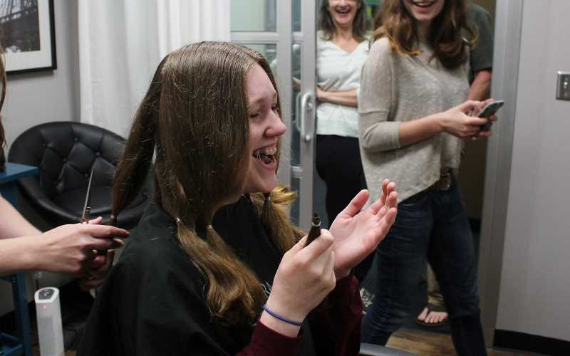 REVIEW PHOTO: KELSEY OHALLORAN - There's no going back now: Tess Creasy reacts as hairdresser Meghan Orrill-Dezell (not pictured) cuts off more than 6 inches of hair for charity.
