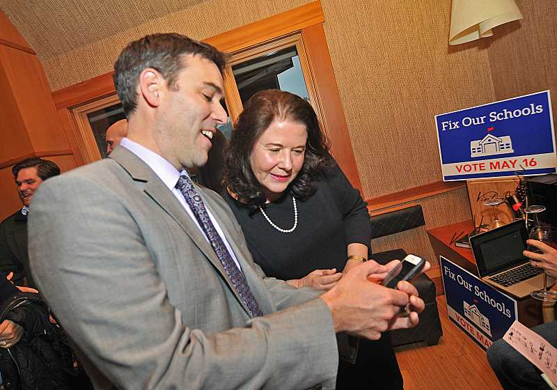 REVIEW PHOTO: VERN UYETAKE - Rob Wagner and Liz Hartman check the early returns during a gathering of bond supporters at the Five Spice Restauranrt in Lake Oswego. Newcomer Wagner and incumjbent Hartman both ran unopposed Tuesday for seats on the School Board.