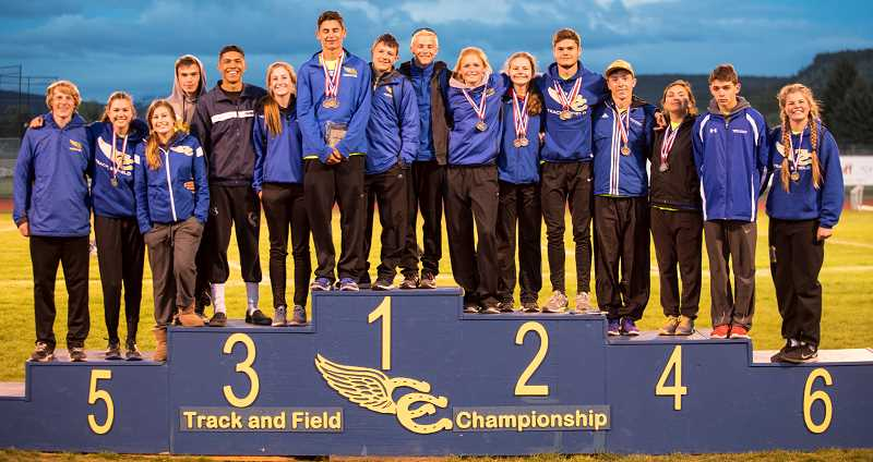 LON AUSTIN/CENTRAL OREGONIAN - Members of the Crook County High School track and field team who qualified for the state championships pose on the podium following the Tri-Valley Conference Championships, which were held Friday and Saturday in Prineville. Team members are (left to right) Jason Slawter, Emma Hehn, Faith Wagner, Noah Carmack, Victor Ramirez, Alyson Thomas, Dominic Langley, Neil Chaney, Noah Chaney, Gracie Kasberger, Mckinzee Mode, Adrien Fournier, Emmett Bailor, Kaeli Hancock, Tyler Lawson and Kenna Woodward. Not pictured, but qualifying for state, is Rylee Troutman.