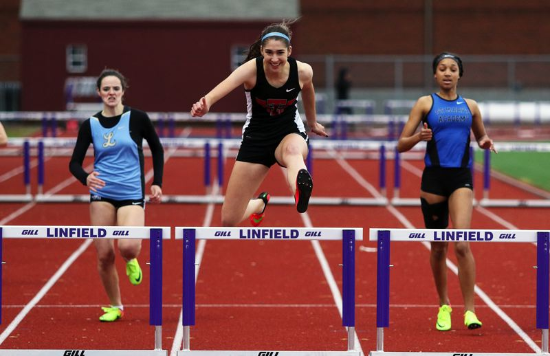 DAN BROOD - Tualatin High School senior Kennedy Oleson has a smile on her face as she clears the final hurdle on her way to victory in the 300-meter low hurdles event Friday at the Three Rivers League district track and field championships.