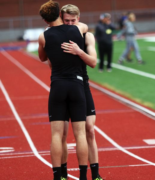 DAN BROOD - Tigard junior Braden Lenzy (left) consoles junior teammate Skylar Holloway following Holloway's injury in the 400 in the TRL district finals.