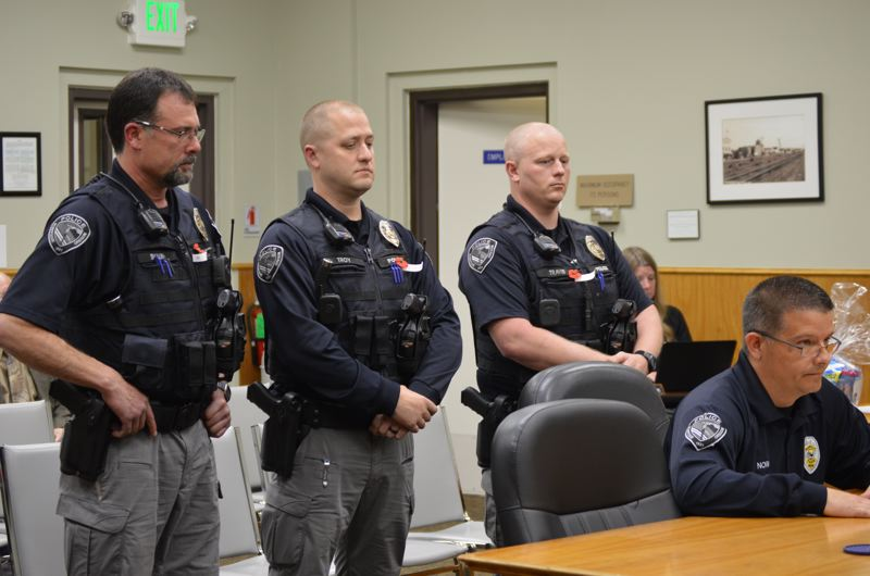 SPOTLIGHT PHOTO: COURTNEY VAUGHN - Officers Shaun Barrett, Troy Gainer and Travis Killens are recognized by Scappoose Police Chief Norm Miller (seated below) during a Scappoose City Council meeting Monday, May 15. Each of the officers will receive plaques for recent incidents where they demonstrated excellent judgement and service while on duty.