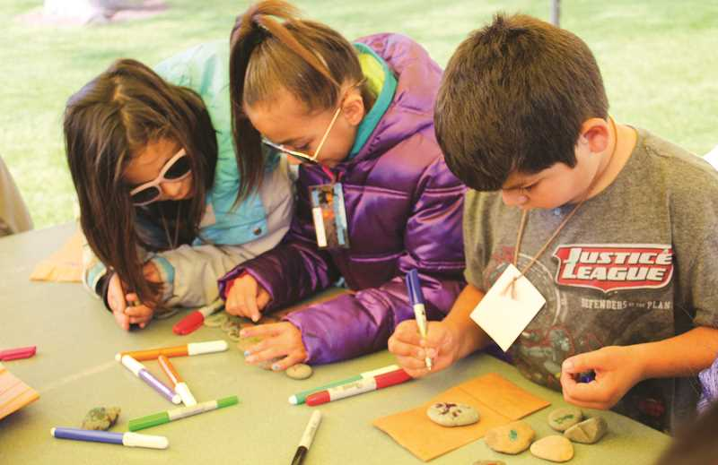 JASON CHANEY/CENTRAL OREGONIAN  - Barnes Butte Elementary first-graders in Jessica DuMoulin's class color ocean rocks at the Tell Me a Story station. Pictured left to right are Jolisa Mendoza, Desiree Lopez and Juan Zarate.
