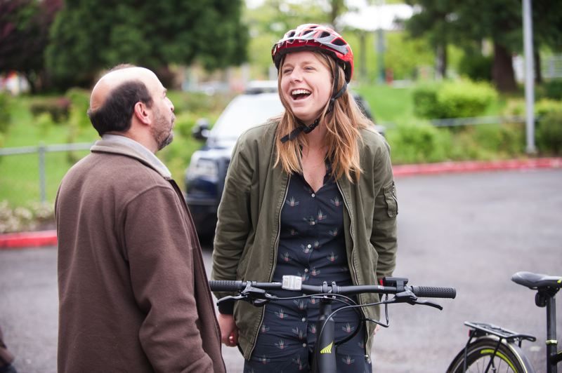 OUTLOOK PHOTO: JOSH KULLA - City of Gresham employee Carly Rice laughs as Rich Fein explains how to operate an electric bicycle Wednesday at Gresham City Hall.