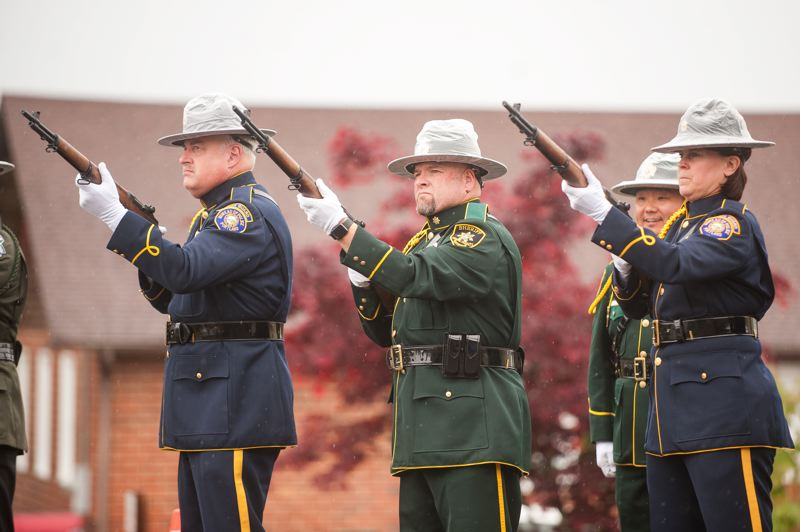 OUTLOOK PHOTO: JOSH KULLA - A ceremonial guard fires a volley of shots last Thursday at the Multnomah County Sheriff's Office annual memorial service for fallen officers.