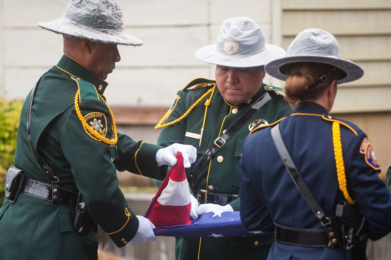 OUTLOOK PHOTO: JOSH KULLA - Members of the honor guard fold the colors on Thursday, May 11, during a ceremony honoring fallen members of the Multomah County Sheriff's Office.