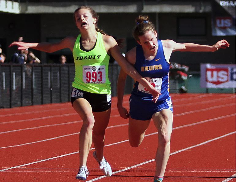 PAMPLIN MEDIA: MILES VANCE - Barlow senior Olivia Johnson leans through the line in a photo finish with Jesuits Makenna Schumacher in Fridays 3,000-meter final. Schumacher won by 0.02 hundredths.
