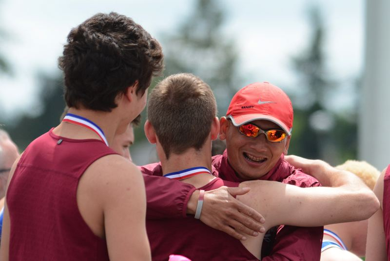 SANDY POST: DAVID BALL - Sandy coach Anouxa Vixathep embraces Dallin Thomas after the team received its first-place medals following its win in the 400-meter relay.