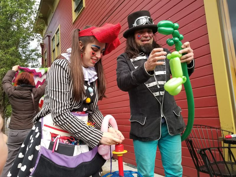 PHOTO BY NIKKI WEST - Professional clowns Olive Rootbeer and Dingo Dizmal make ballon animals for eager children at Milwaukie's First Friday event.