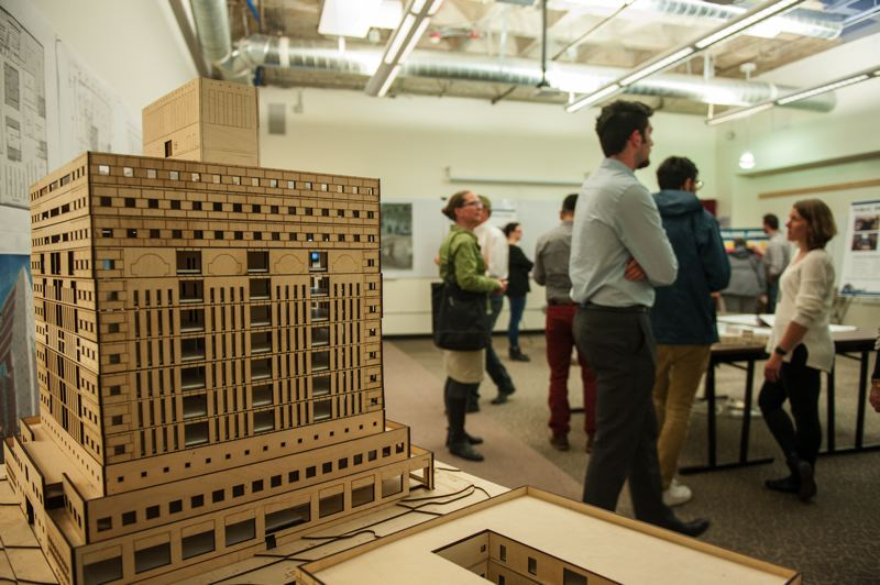 COURTESY: CITY OF PORTLAND - Stakeholders and the public mingled at a recent open house to look at plans for therenovation. A laser cut wooden model with the top two floors removed showed the new floor plan, with break out rooms, telephone booths and open plan offices.  At right, in white, City Project Manager Kristin Wells talks to a visitor.