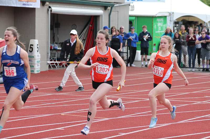 PIONEER PHOTO: CONNER WILLIAMS - Molalla sophomore Emma Andrews (left) takes the baton from freshman Hannah Henderson in the 4x100 meter relay at the state meet Saturday. The Indians took fourth in the event.