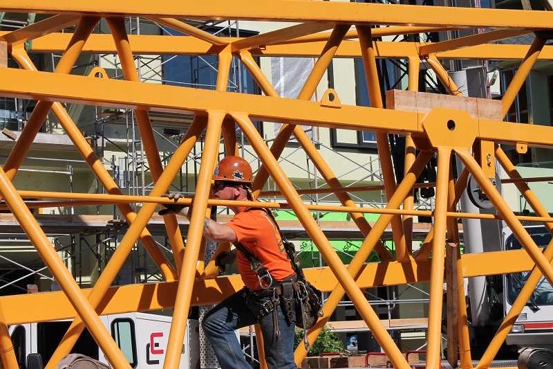 REVIEW PHOTO: ANTHONY MACUK - The main jib arm of the Wizer Block's 212-foot-tall tower crane was disassembled in segments that were then loaded in pairs onto a series of trucks parked on First Street.
