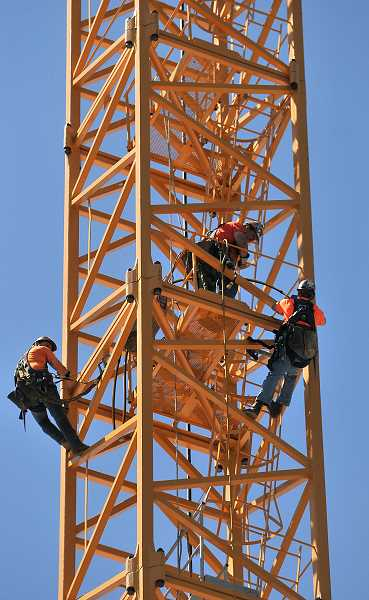 REVIEW PHOTO: VERN UYETAKE  - Workers prepare the tower portion of the Wizer Block crane for dismantling Tuesday afternoon. It was the last part of the 212-foot-tall structure to come down.