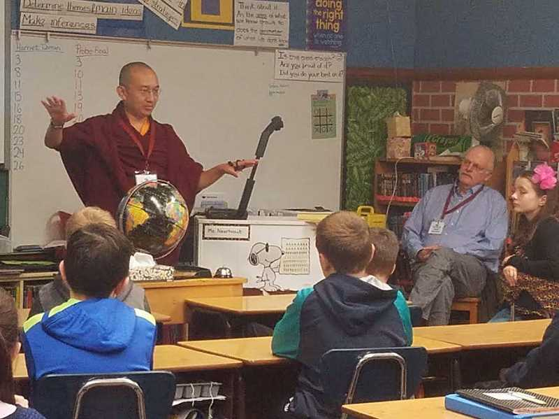 SUBMITTED PHOTO: COURTESY OF AMY BLAKEY - Tenzin Tsultrim Palden, also known as Khangser Rinpoche (which means yellow house), a Buddhist monk from India, visited the fifth-grade classes at Forest Hills Elementary last week. Lake Oswego Rotary Club member Mark Waller and the students listen as the holy man shares information on meditation and controlling bad emotions.