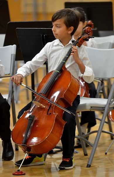 TIDINGS PHOTOS: VERN UYETAKE - A West Linn-Wilsonville strings student plays the cello during the districts final concert of the year Wednesday, May 17 at Wilsonville High School.