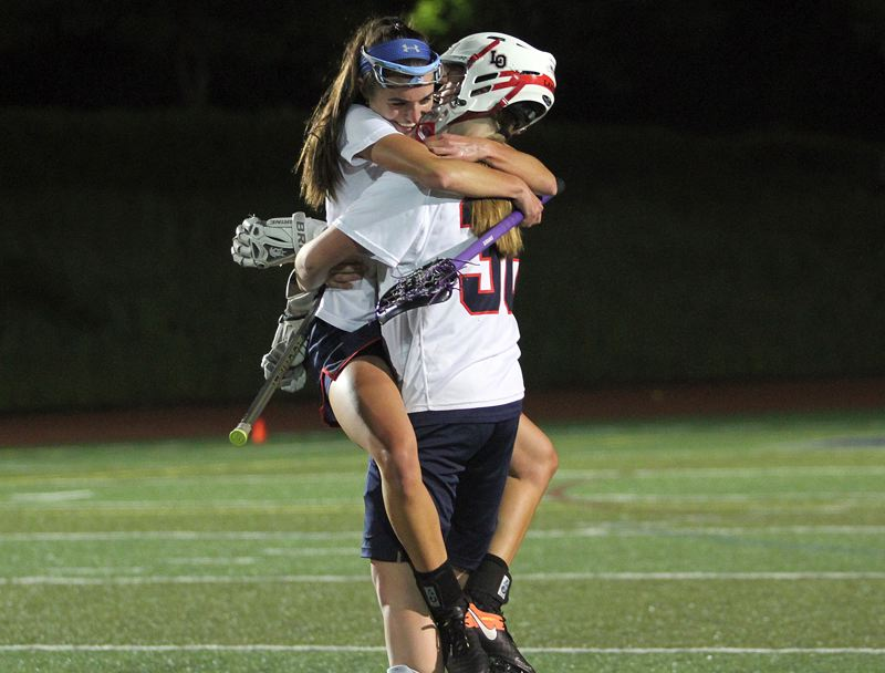 REVIEW PHOTO: MILES VANCE - Lake Oswego senior Lauren Gilbert jumps into the arms of fellow senior goalie Riley Hertford at the end of their team's 13-3 win over Oregon Episcopal in the Oregon Girls Lacrosse Association state championship at Wilsonville High School on Thursday.