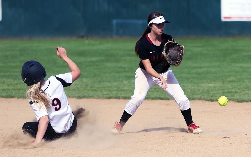 DAN BROOD - Tualatin freshman shortstop Bella Valdes (right) looks to grab the ball as McMinnville sophomore Lexie McKinley slides to second base in the first inning of Wednesday's playoff game.