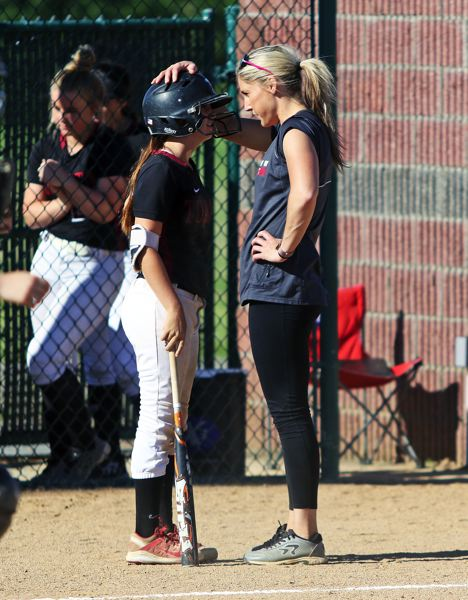 DAN BROOD - Tualatin coach Jenna Wilson (right) talks to freshman Bella Valdes before her at-bat during Wednesday's state playoff game.